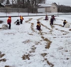 kids rolling snowballs in the school yard